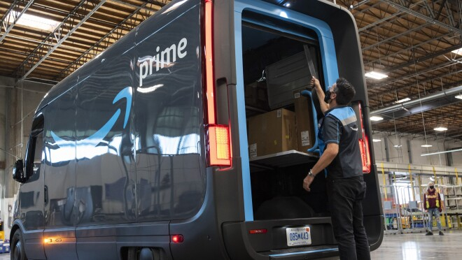 An Amazon delivery driver closes the back door of a Prime-branded Rivian van.