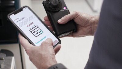 Michael Snyder, PhD, professor and chair of genetics for Stanford University's School of Medicine holds his smartphone showing the results of tested diagnostics. In his other hand he holds a black testing device.