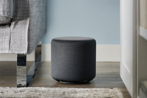 An Echo Sub sits on a wood floor in a living room. To the left is a sofa. To the right, cabinets.