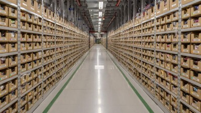 Interior of an Amazon fulfillment center in Singapore. Product is stored in containers on either side of an aisle.