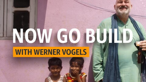 Werner Vogels, CTO of Amazon stands besides two young children in India