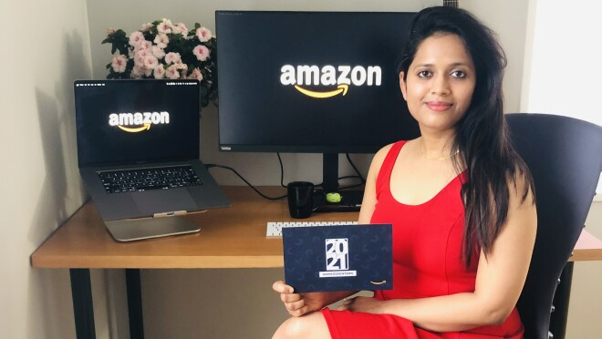 An image of a woman smiling for a photo while sitting at her desk in her home. She has two computer monitors in the background with the Amazon logo on their screens, and she is holding an invitation to the 2021 Amazon internship class.