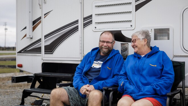 A man and woman sit together and laugh outside a RV.