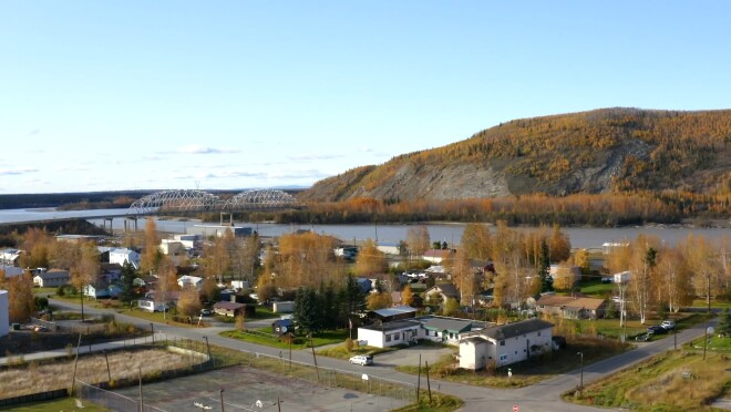 Aerial view of a small town built next to water and a large hill.