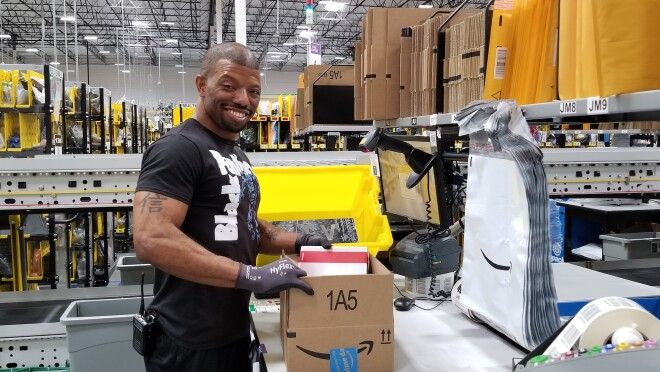 Amazon fulfillment center employee at a packing station