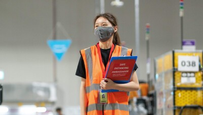 """A woman wearing an orange safety vest and a face mask stands in an Amazon fulfillment center, carrying a clipboard that says """"safe distancing ambassador."""""""