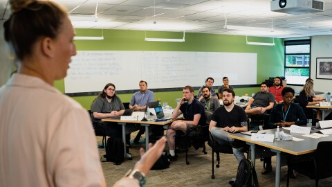 A woman stands at the front of a classroom as she speaks to around a dozen individuals who are seated across the room.