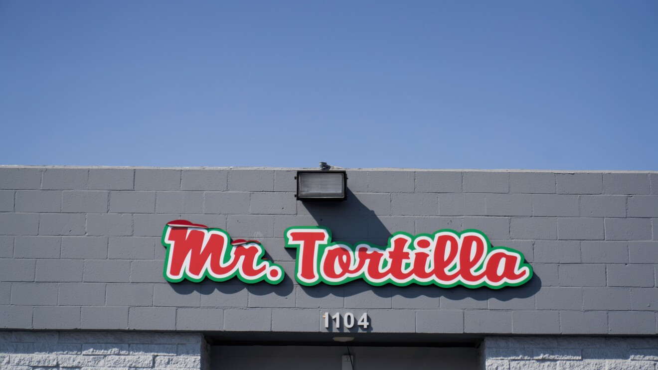 A red Mr. Tortilla sign hangs above the door of the Mr. Tortilla warehouse.