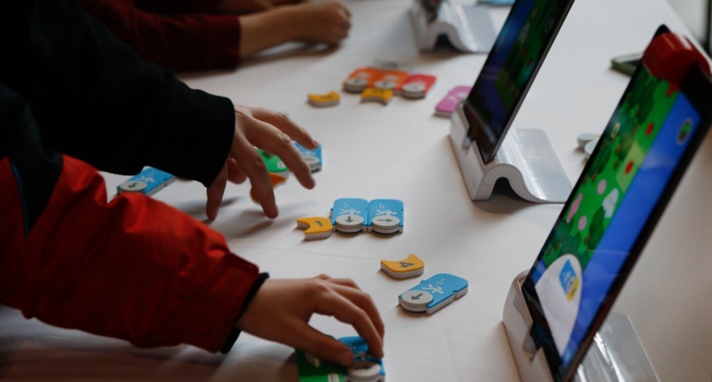 Children hold wooden game pieces, with a tablet placed on the table in front of them.