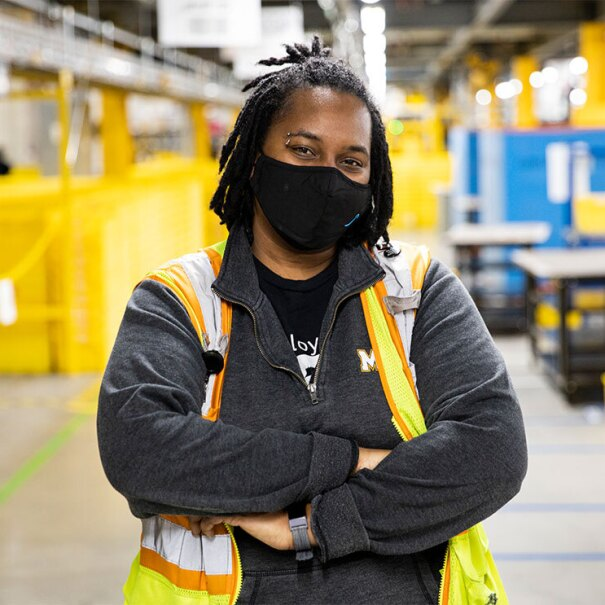 An Amazon employee stands in a fulfillment center with a mask on, looking at the camera.
