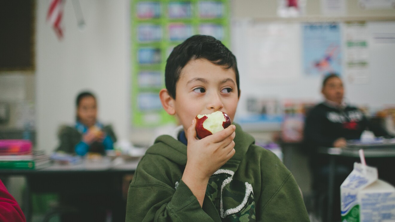 A boy in a classroom is eating an apple. Behind him, other students are seated at desks.