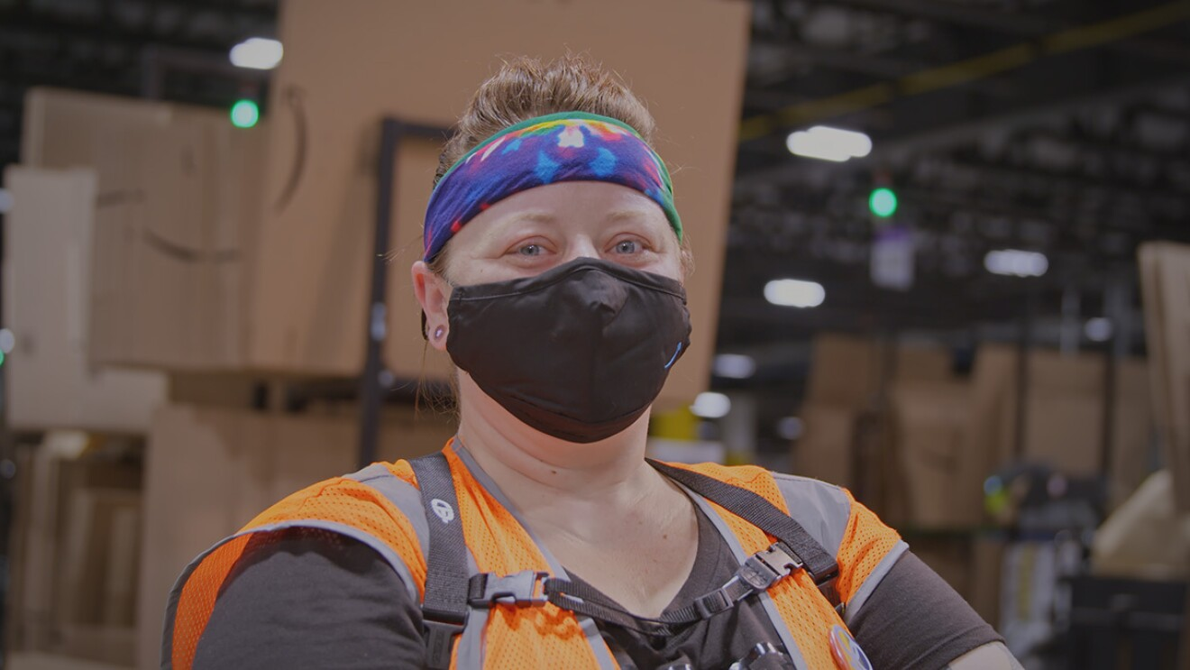 An Amazon associate wearing a mask, a high visibility vest, and a tie-died headband poses in front of a stack of flat-packed cardboard boxes in an Amazon fulfillment center