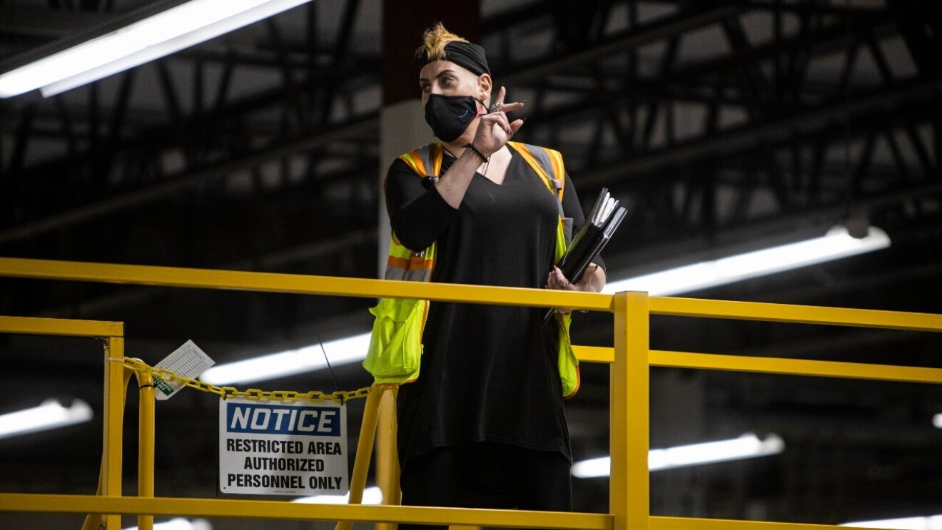 An image of an amazon employee standing in a fulfillment center wearing a mask and a safety vest while giving instructions to fellow employees.