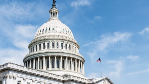 An image of the United States Capitol Building, home of Congress. There is a blue sky behind the building and an American flag flying on its roof.