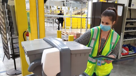 A woman wearing a safety vest and mask inspects a hand-washing station.
