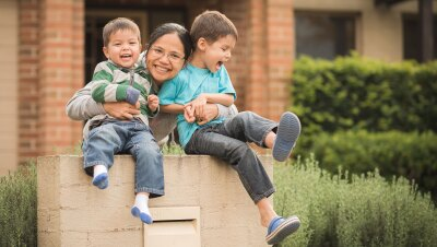 A family of a mom hugs her two boys while smiling for a photo outside of their home.