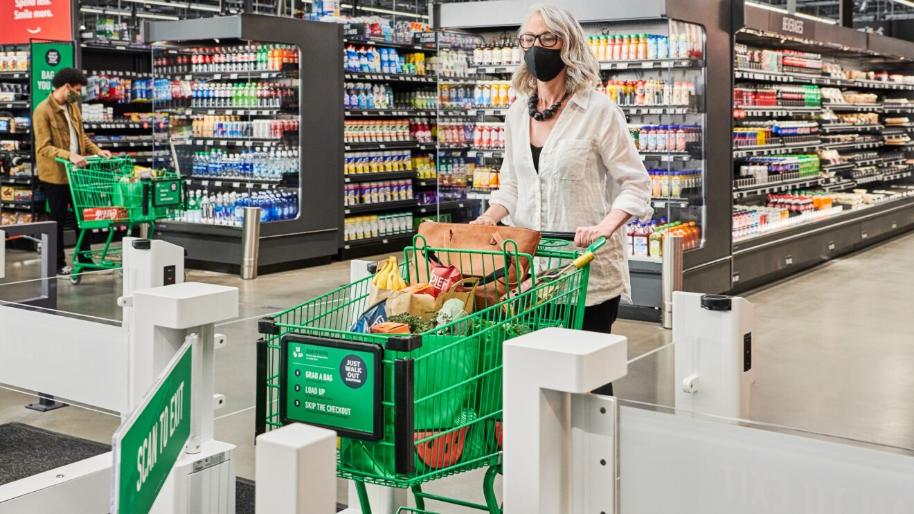 A woman with short curled blonde hair pushes her green grocery cart filled with bags of grocery and her purse through the exit of the Just Walk Out gates.