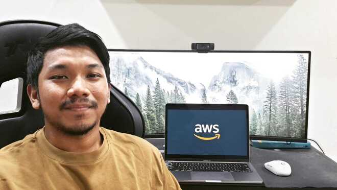 An image of a man smiling for a photo while sitting at his desk in his home. His laptop monitor in the background has the Amazon logo on it.