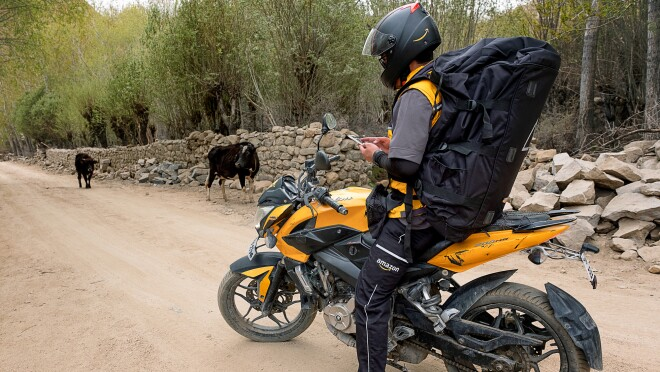 A motorcyclist wearing a large black backpack and an Amazon delivery uniform stands astride a motorcycle on a dirt road. He looks down and checks his smartphone. Two cows are in the background of the image.