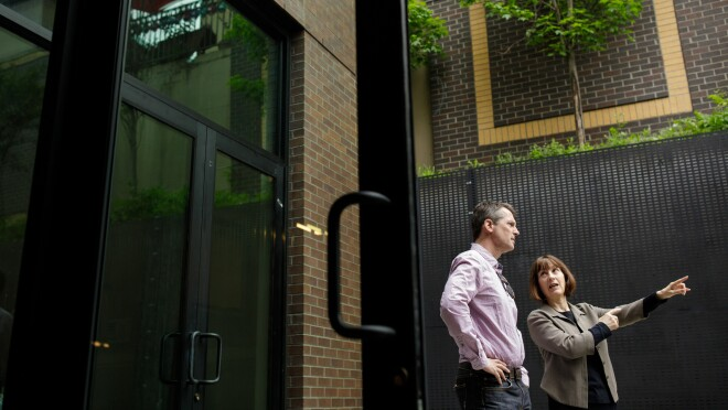 Seen through a glass door, a man and a woman stand in an open-air courtyard. The woman points to something to the right. A tree and a brick wall are at the top of the image.