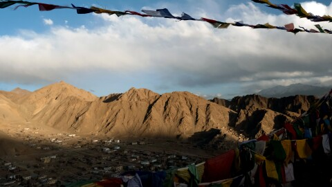Prayer flags flutter in a breeze. In the background there is a valley with buildings. Mountains rise up in the distance.