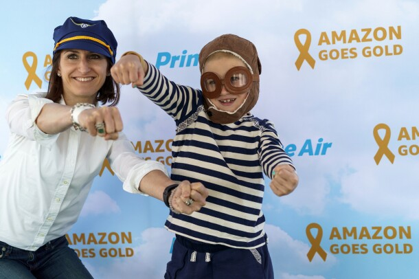 A young boy wearing a costume of aviator cap and goggles, next to his mother, wearing a pilot's hat, post in front of a Prime Air backdrop.