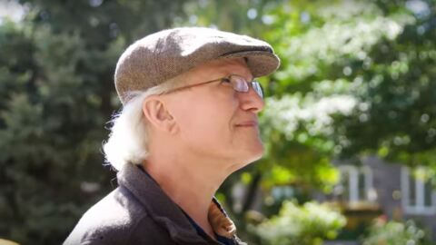 A retired gentleman sits on a park bench, looking upward. He wears a jacket and newsboy cap.