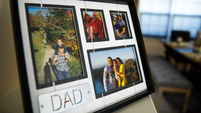 """A picture frame with four separate family photos. The word """"dad"""" is in all-capital letters in the bottom left of the frame."""