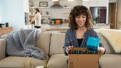 An Amazon customer smiles as they unbox a package on their couch.