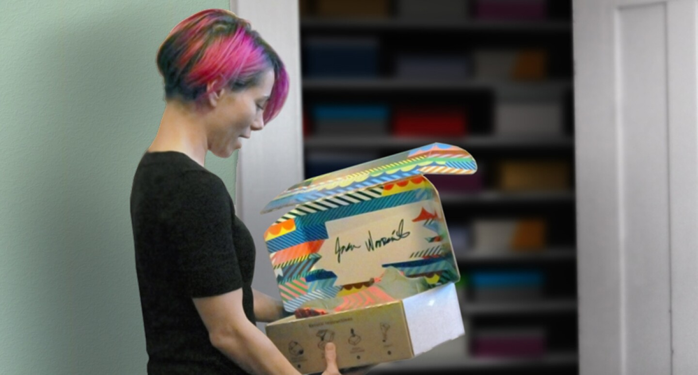 A woman is holding a new Amazon package that is designed to be reversible.