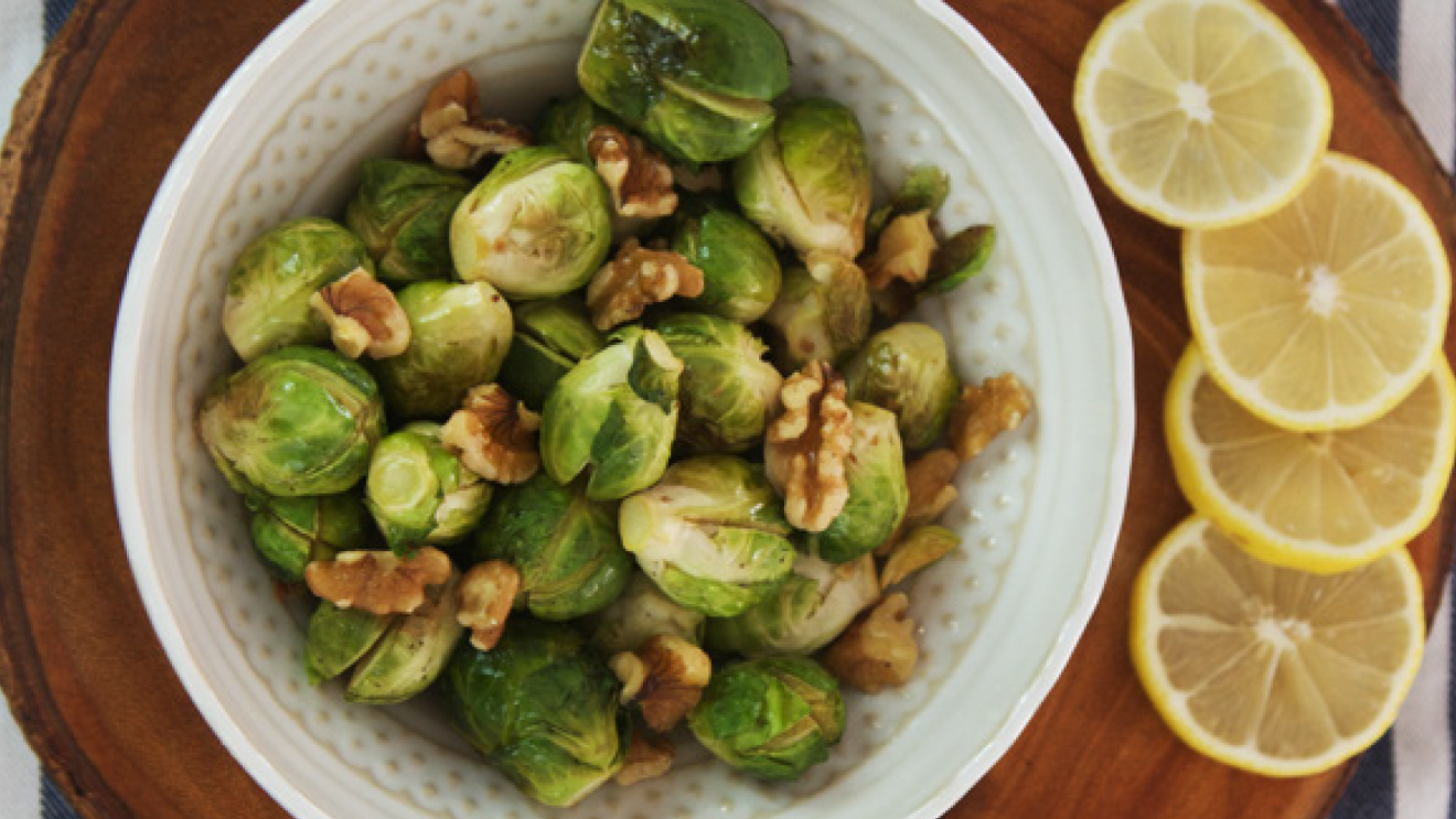 An image of brussels sprouts with walnuts on them in a plate sitting on a cutting board with lemon slices next to them.