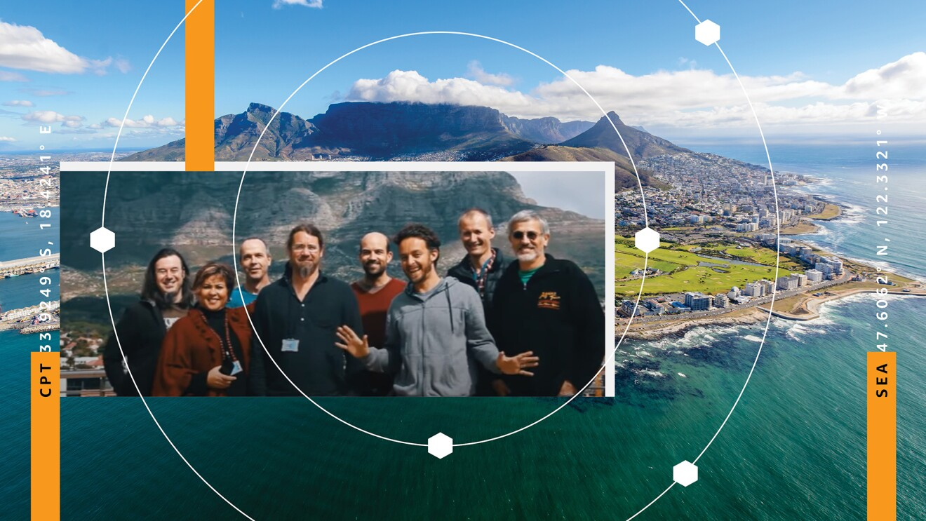 An image of mountains and ocean in South Africa. Over top of the image is another image of a group of eight employees smiling for a group photo.