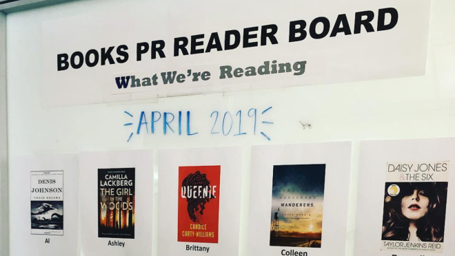 An image of the Books PR Reader Board, a whiteboard featuring her team's favorite books from the month.