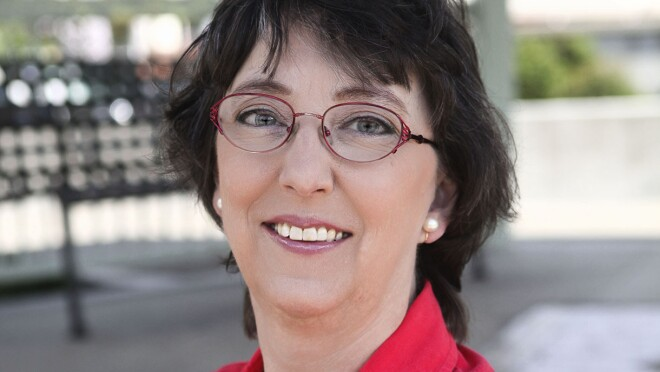 A woman wearing glasses and a red button up shirt smiles at the camera.