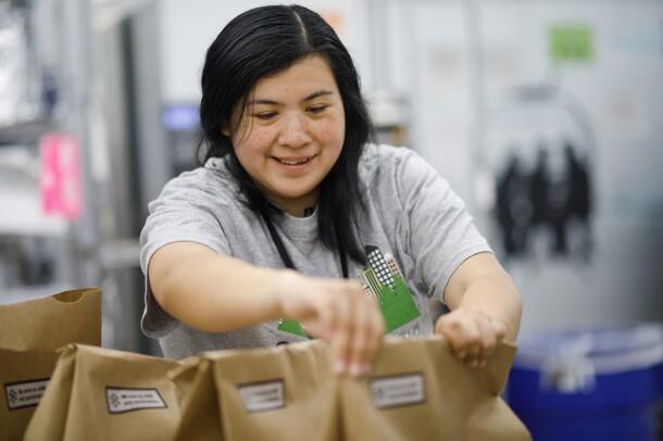 Prime Now associate Erika Lopez arranges brown paper shopping bags.