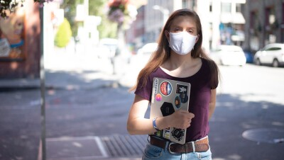 A woman stands on the street with a mask on, looking at the camera. She is holding a laptop with stickers related to Amazon and AWS.