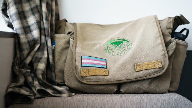 An earth-tone canvas messenger bag sits atop a padded surface. In the lower left section of the bag's flap, there is a patch of a flag with five horizontal stripes: white in the center, sandwiched by pink, with light blue at the top and bottom. This is the Transgender Pride Flag.