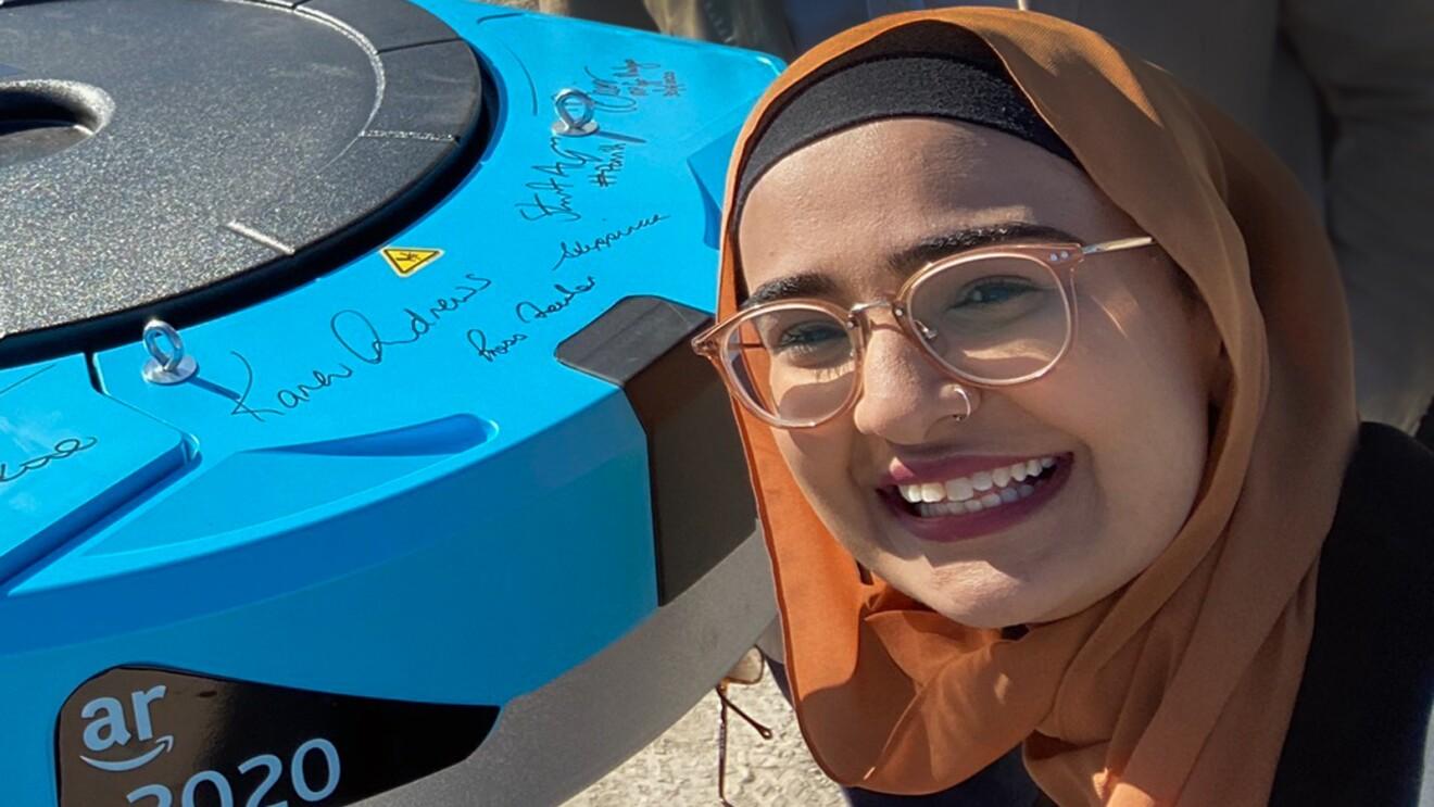 A woman poses with an Amazon Robotics unit.