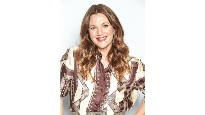 Drew Barrymore smiles wearing a patterned shirt.