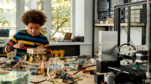 A young boy works on a robotics project in his garage.