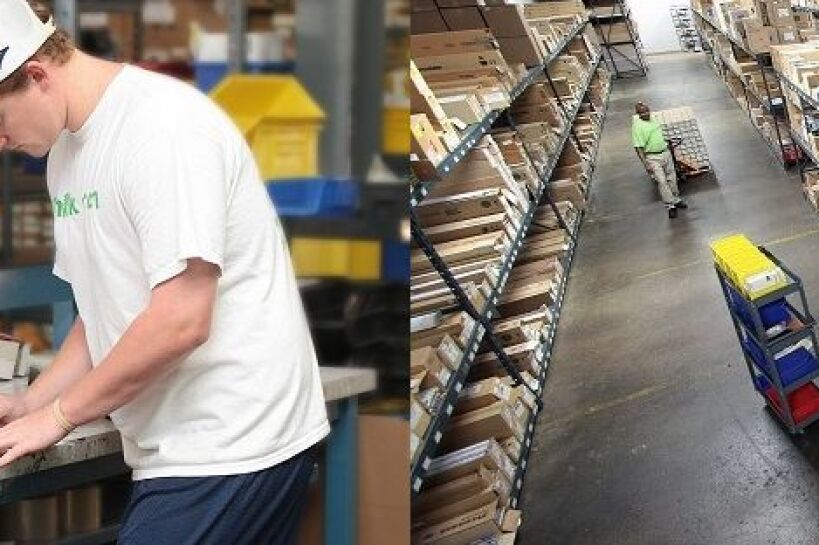A man in a baseball cap inside of a warehouse full of boxes.