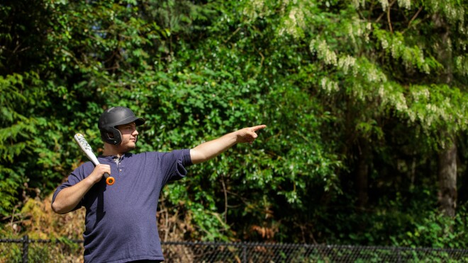 A man balances a baseball bat on his shoulder. He wears a batting helmet. With the hand that's not holding the bat, he points up and away toward the spot he plans to hit the ball.