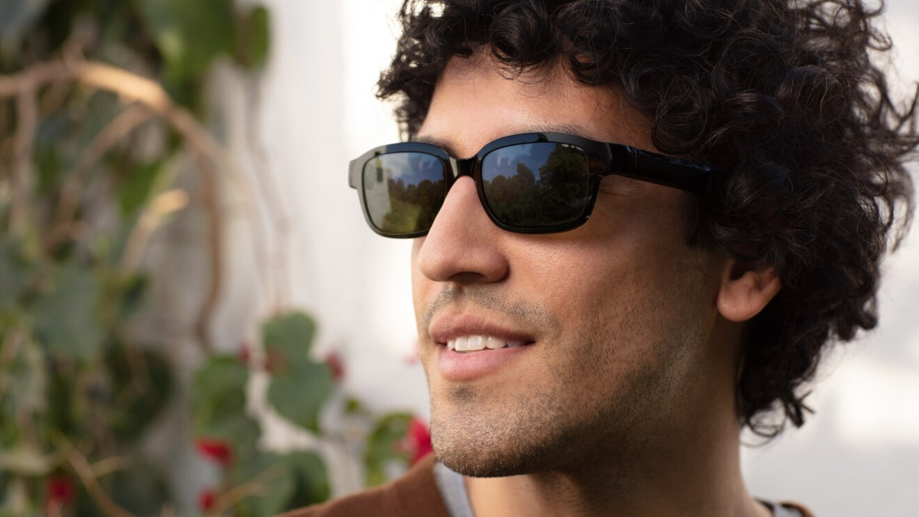 A  man wears black Echo Frames with sunglass lenses. He is looking to his right and grinning.