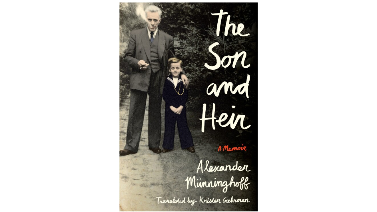 """The book cover of """"The Son and Heir"""" features a vintage image of a an older man blowing smoke out of his mouth holding a pipe in one hand and his other arm is around the arm of young boy. The older man wears a suit and the younger boy wears a sailor-like suit. They stand on a dirt path surrounded by trees."""