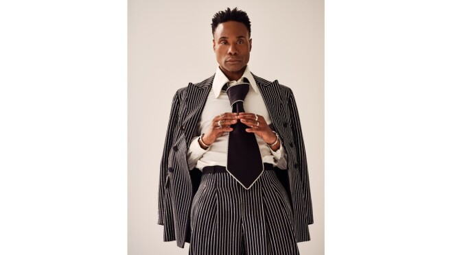 Billy Porter wears a striped suit with an oversized black tie.