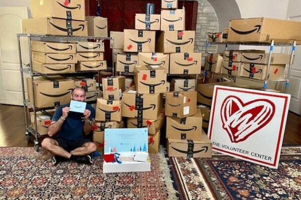 "An image of Amazon boxes stacked up with a man sitting in front of the boxes holding the Delivering Smiles invitation for charities selected for this year's campaign. There's also a sign with a big heart and ""The Volunteer Center"" on it."