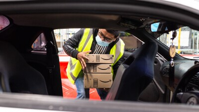 An Amazon Flex driver removes 3 Amazon boxes from the back of his vehicle. He wears a yellow safety vest and mask.