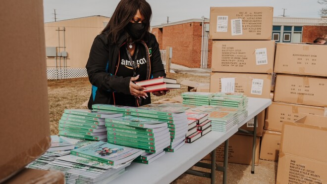 Nancy Dalton stacking books on a table while wearing a mask. There are boxes of books around her.
