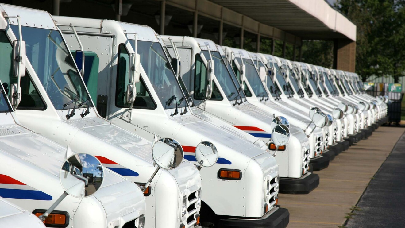 More than a dozen United States Postal Services delivery vehicles lined up under the canopy of a Postal Service building.