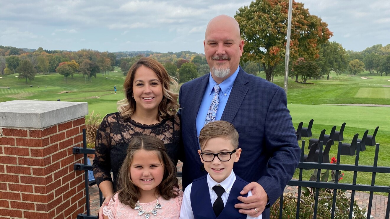 A family of four stand on a pavilion, dressed up, and smile at the camera.